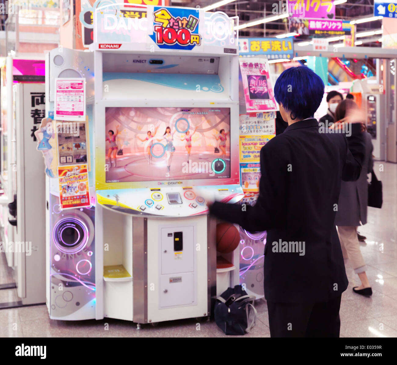 Girl playing dance station slot machine at arcade in Odaiba, Tokyo, Japan - Stock Image