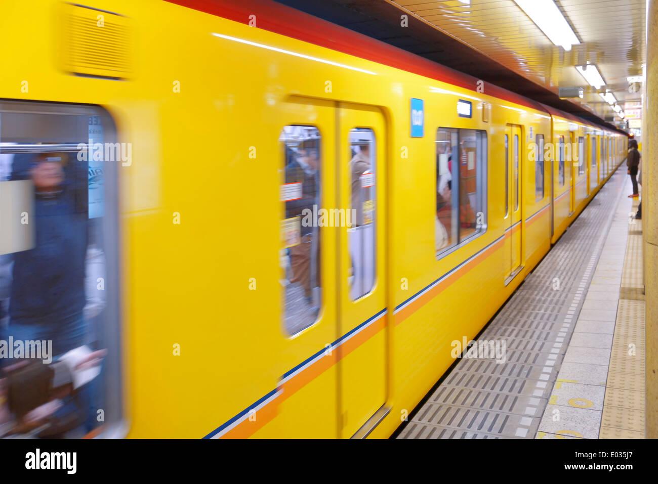 Tokyo Metro yellow subway train arriving to a subway station platform. Tokyo, Japan. - Stock Image