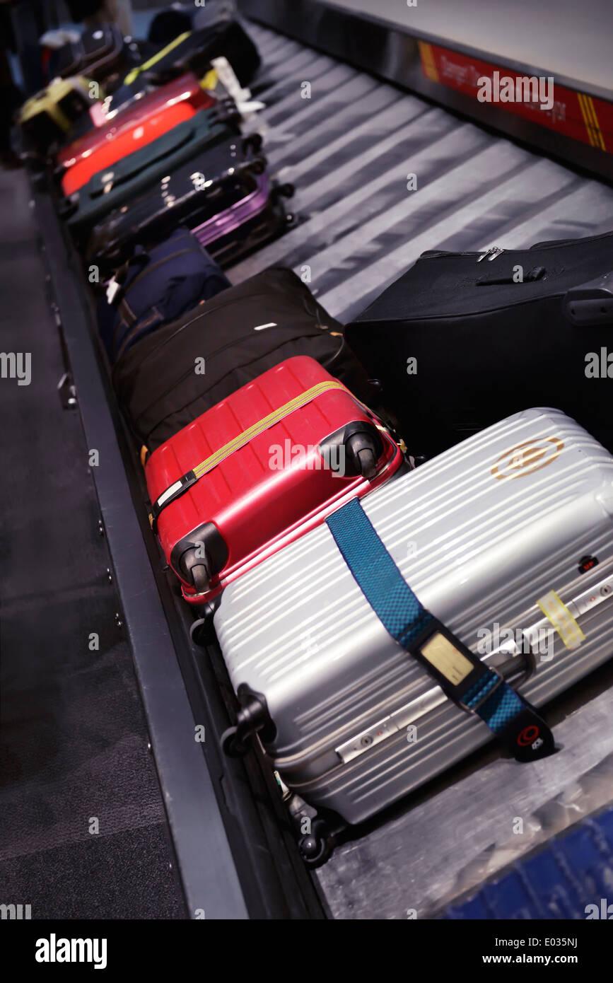 Row of suitcases on airport baggage claim conveyor carousel, Toronto Pearson International Airport, Ontario, Canada - Stock Image