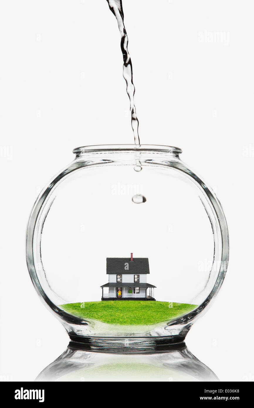 Water pouring on a house in a fishbowl - Stock Image