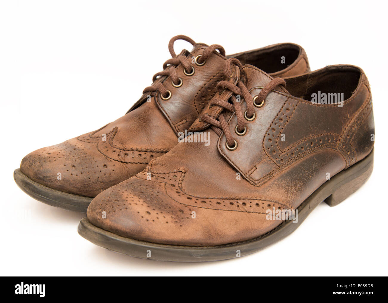 Old worn out brown shoes isolated on a white background - Stock Image