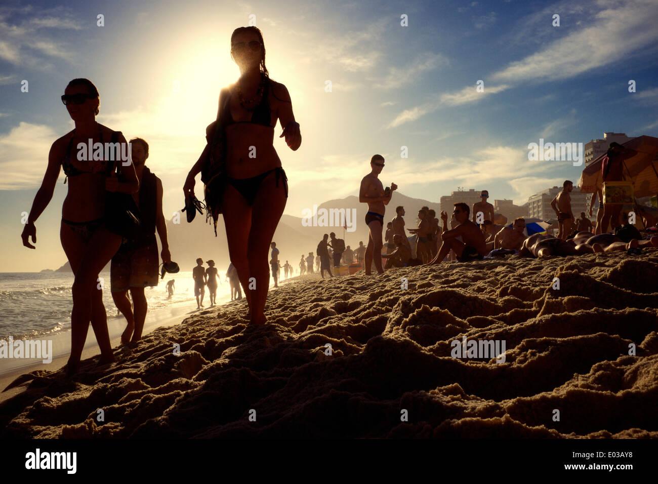 RIO DE JANEIRO, BRAZIL - FEBRUARY 21, 2014: Silhouettes of men and women walking along Ipanema Beach at sunset. - Stock Image