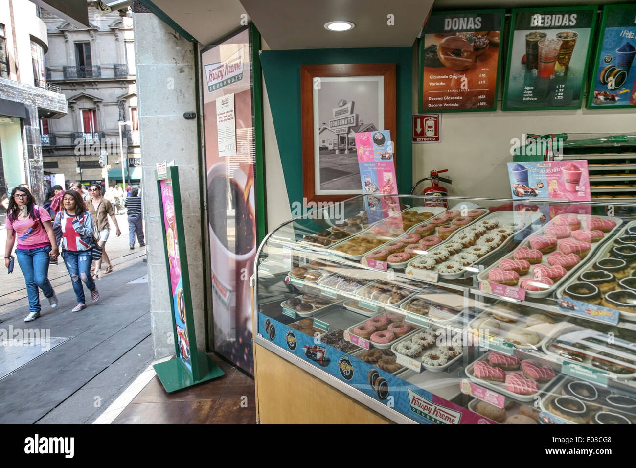 Krispy Kreme doughnut display in shop open to pedestrian Calle Madero to lure passers by walking in Centro Historico Mexico City - Stock Image
