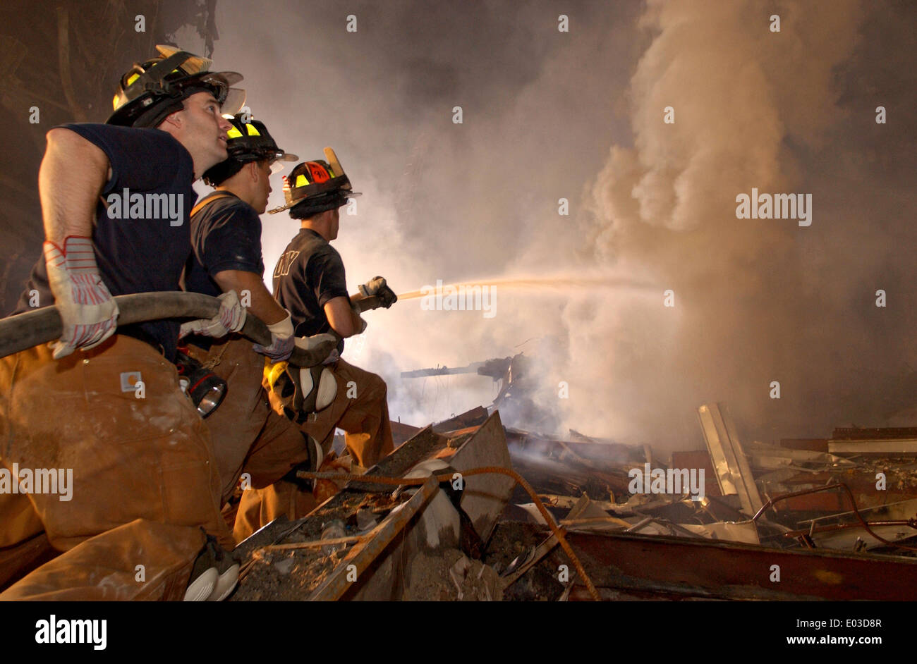 New York City Firemen battle fires amongst the wreckage of the World Trade Center in the aftermath of a massive terrorist attack which destroyed the twin towers killing 2,606 people September 19, 2001 in New York, NY. - Stock Image
