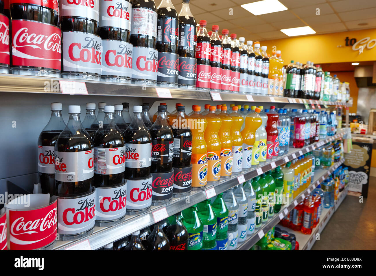 rows of 2 litre bottles of fizzy drink on display in a filling station convenience store in northern ireland - Stock Image