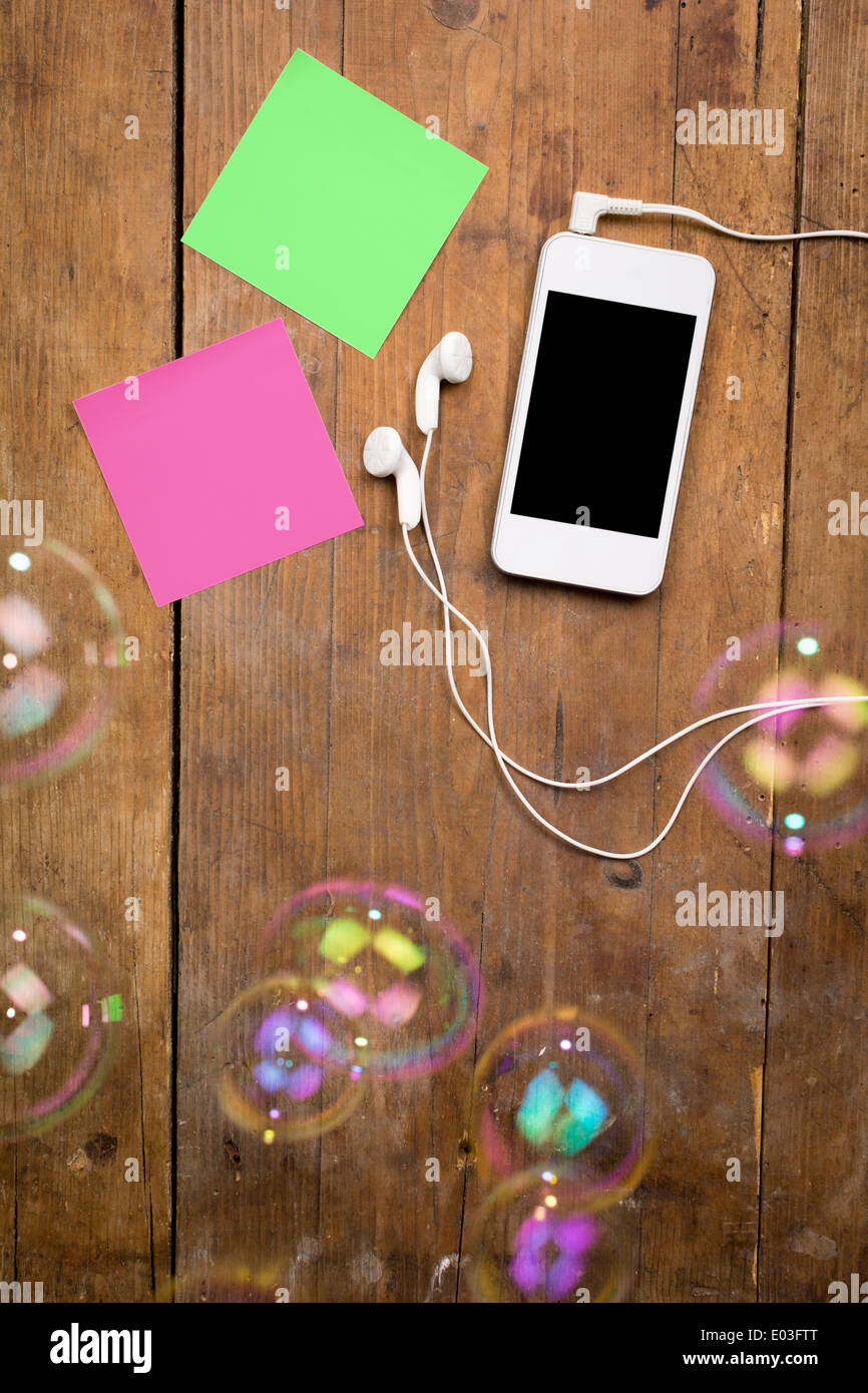 White smart phone and sticky notes on brown wooden background - Stock Image
