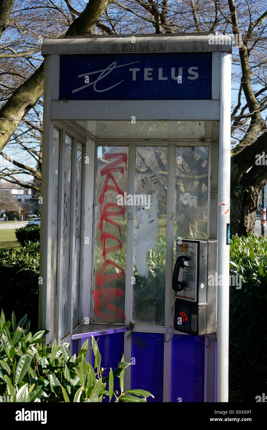 Defaced pay telephone booth in Vancouver, BC, Canada - Stock Image