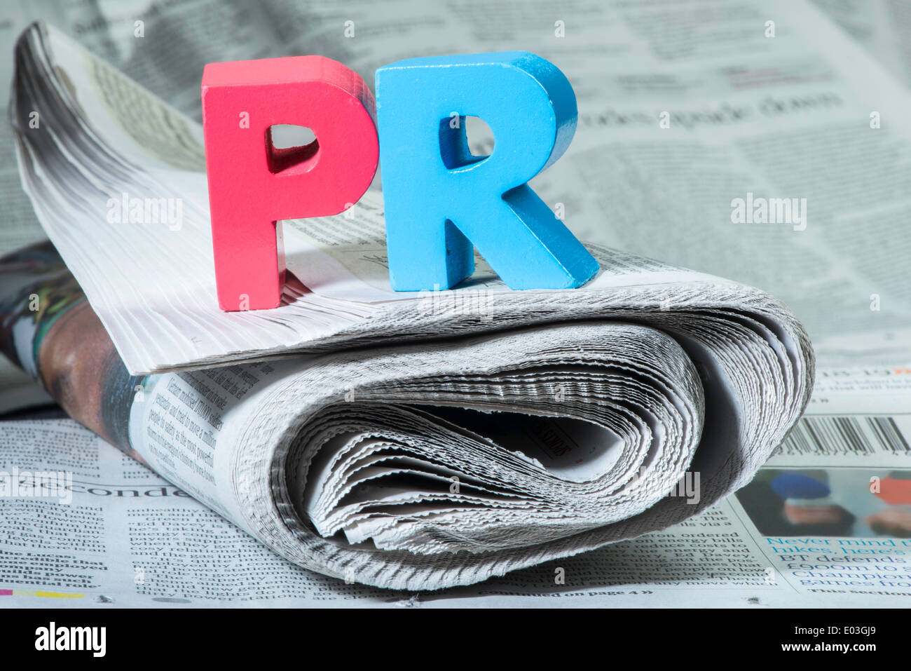 Word PR on newspaper. Wooden letters - Stock Image