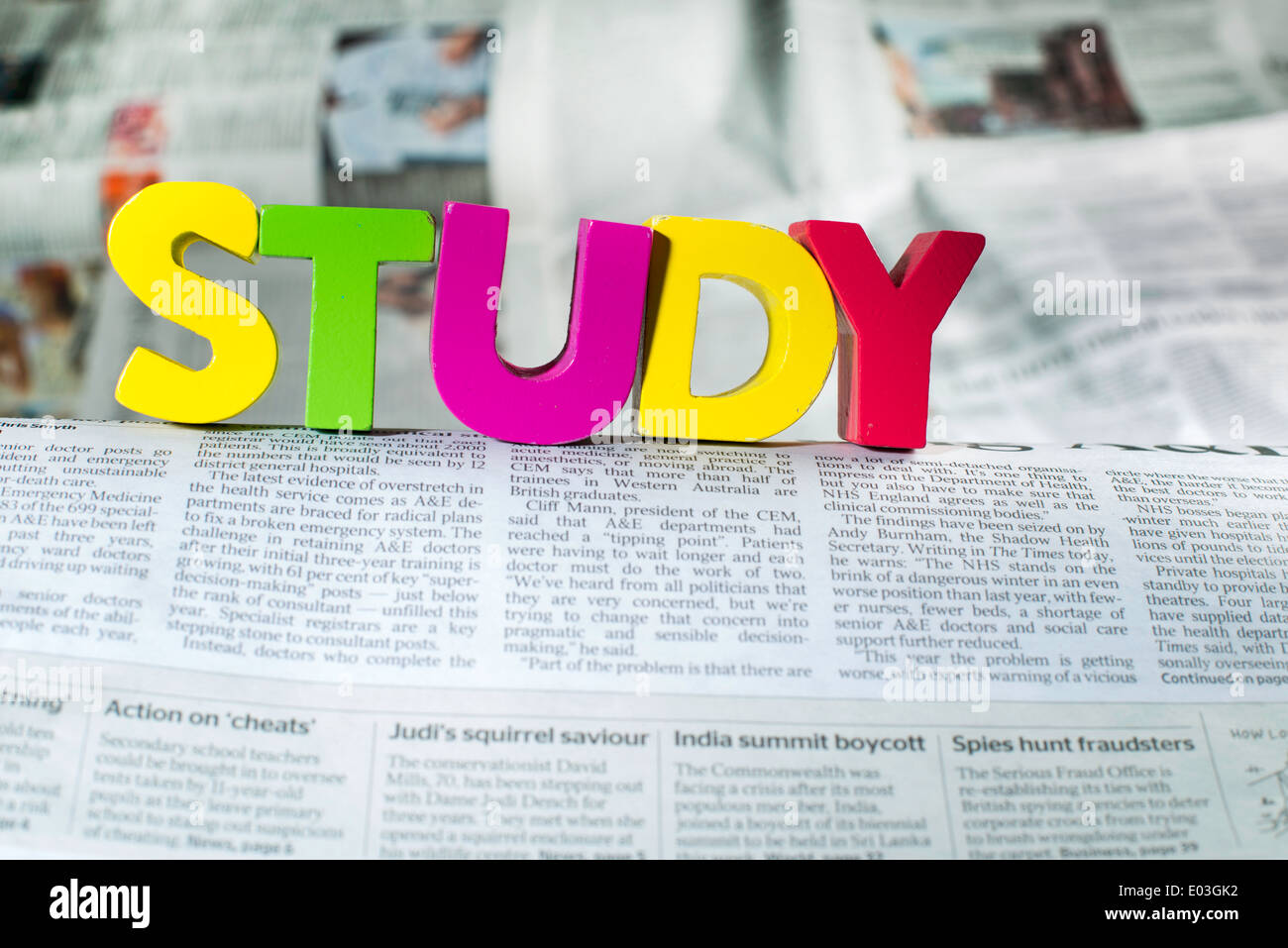 Word study on newspaper page. Wooden letters - Stock Image