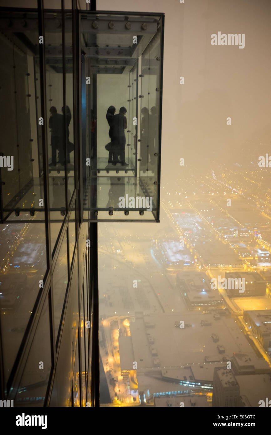 People enjoy the nighttime view from the Ledge in the Willis Tower in Chicago. - Stock Image