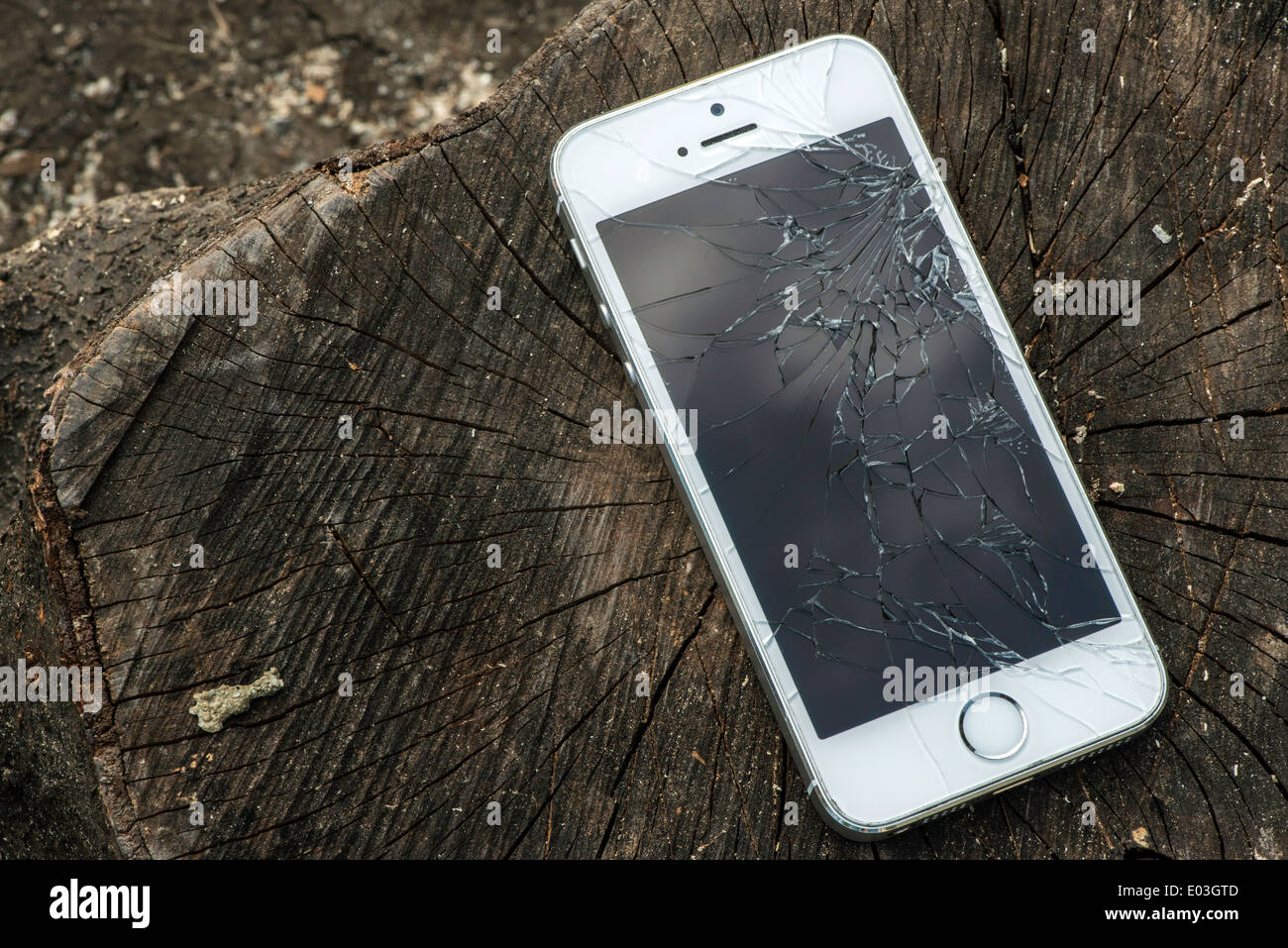 Broken white iphone glass on wood - Stock Image
