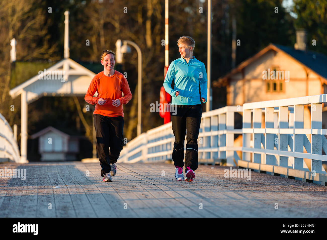 Two women jogging together along the bridge at sunrise - Stock Image