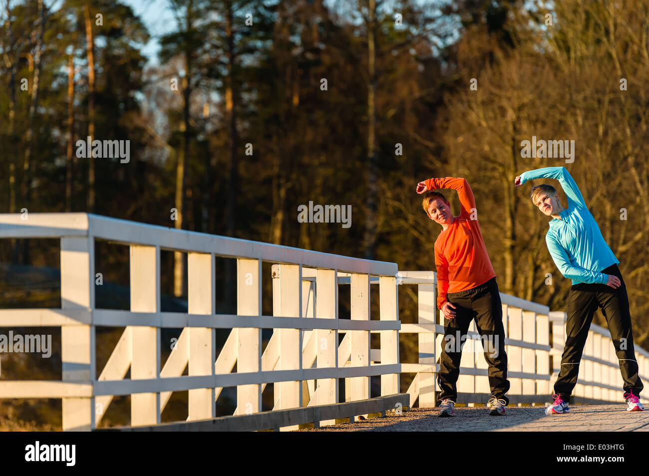Two women stretch together on the bridge at sunrise - Stock Image