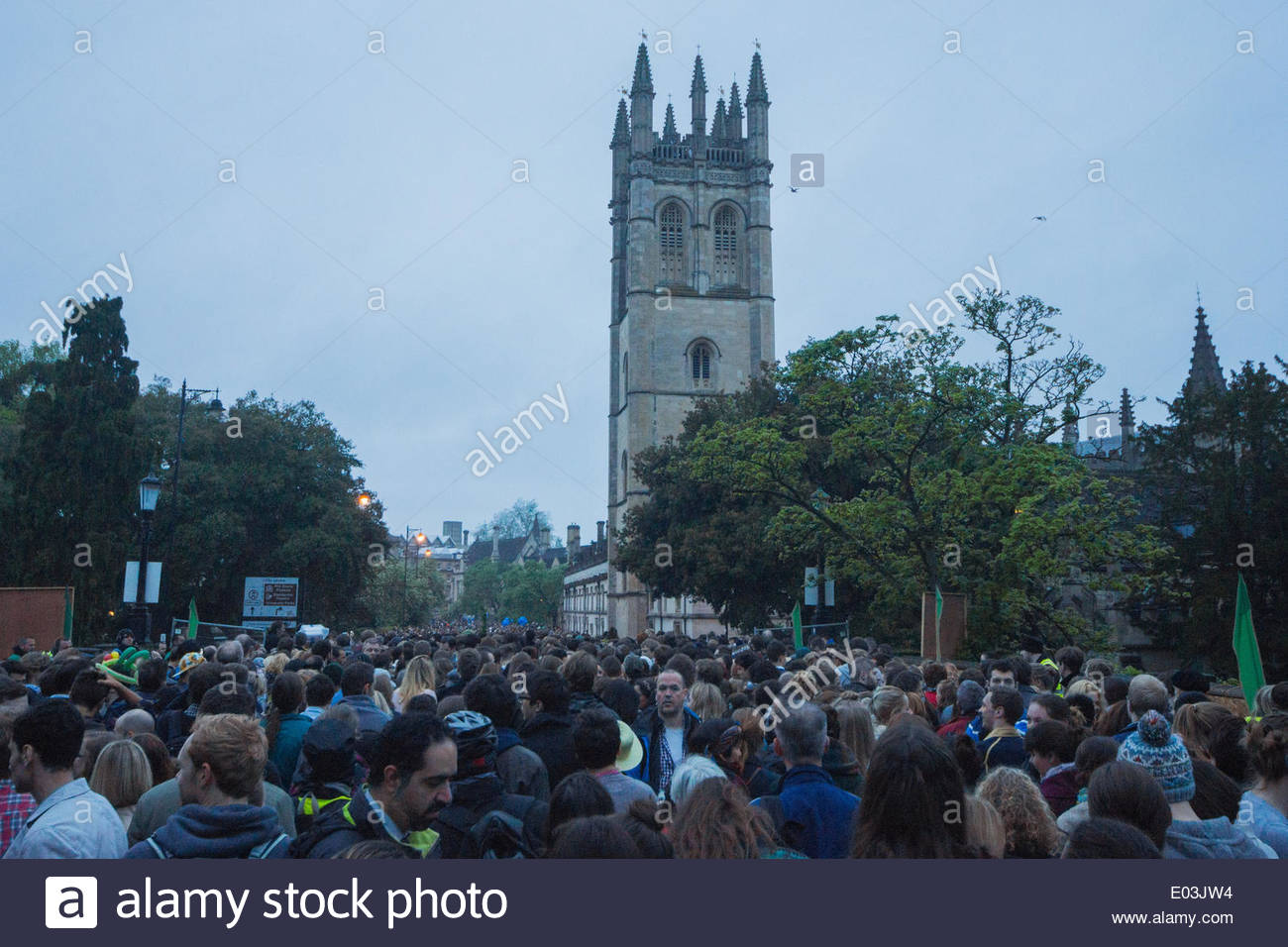 Oxford, UK. 01st May, 2014. Thousands gather to hear Magdalen College School Choir sing madrigals at 6am from the tower of Magdalen College overlooking Magdalen Bridge on the River Cherwell in Oxford. The traditional celebration of Beltane on May 1st is an annual event, with pubs and restaurants open all night, with music and Morris Men performing in the street. Revellers often stay out all night from Balls in College the night before. Credit:  Greg Blatchford/Alamy Live News - Stock Image