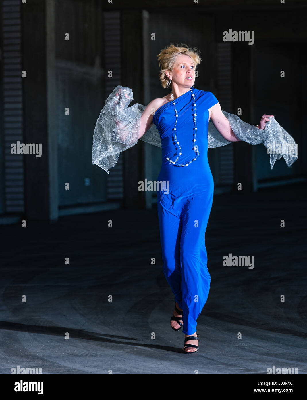Frightened woman wearing blue dress and running in the public parking house - Stock Image