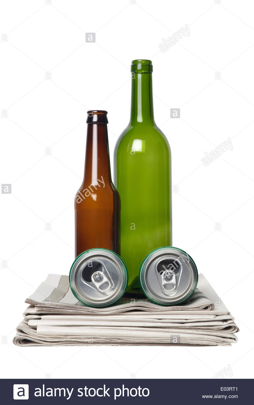 Recycling items glass bottles cans newspapers studio shot - Stock Image