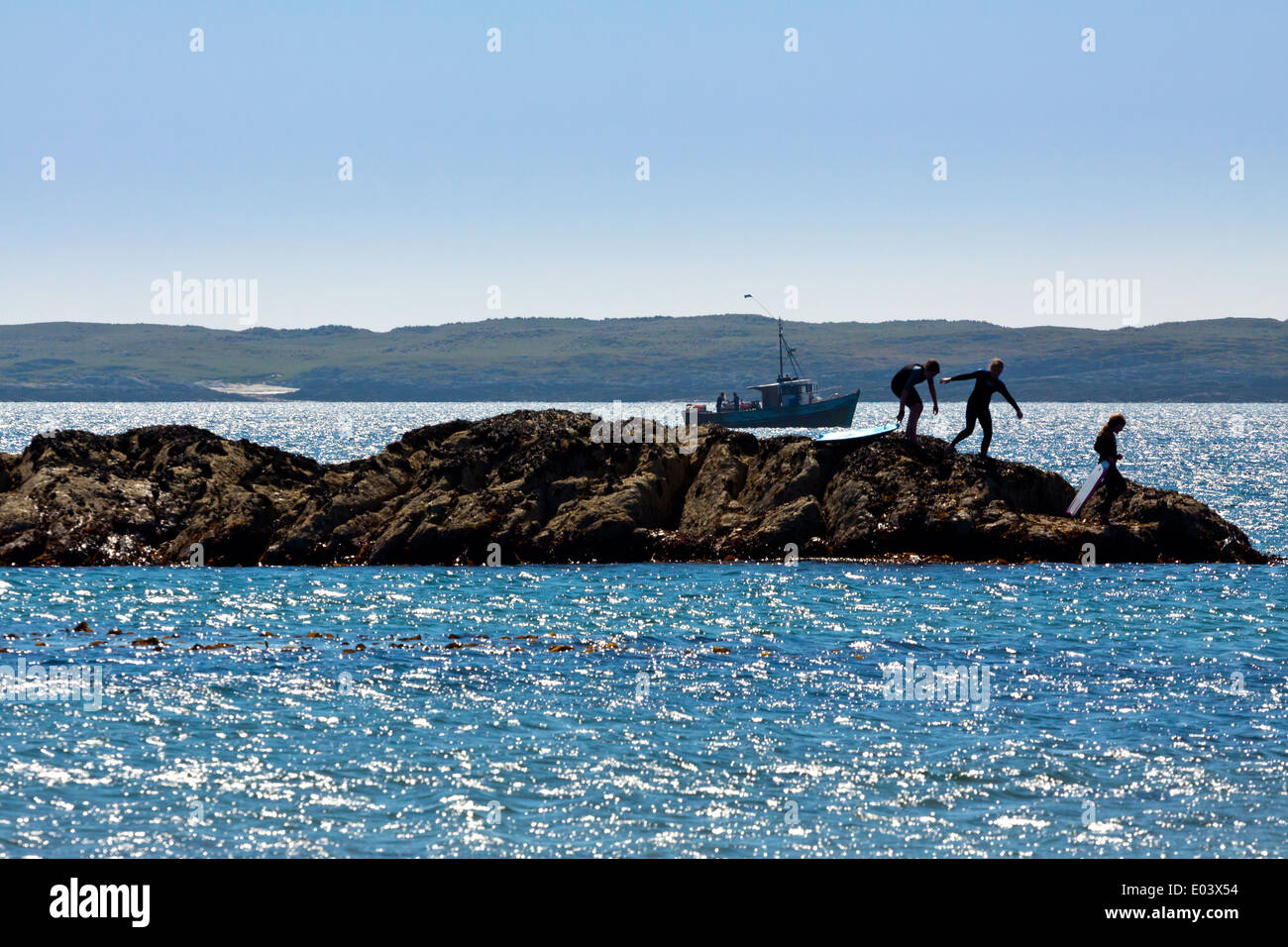 Children playing on rocks on a beach on Isle of Coll Inner Hebrides Argyll and Bute Scotland UK with fishing boat in background Stock Photo
