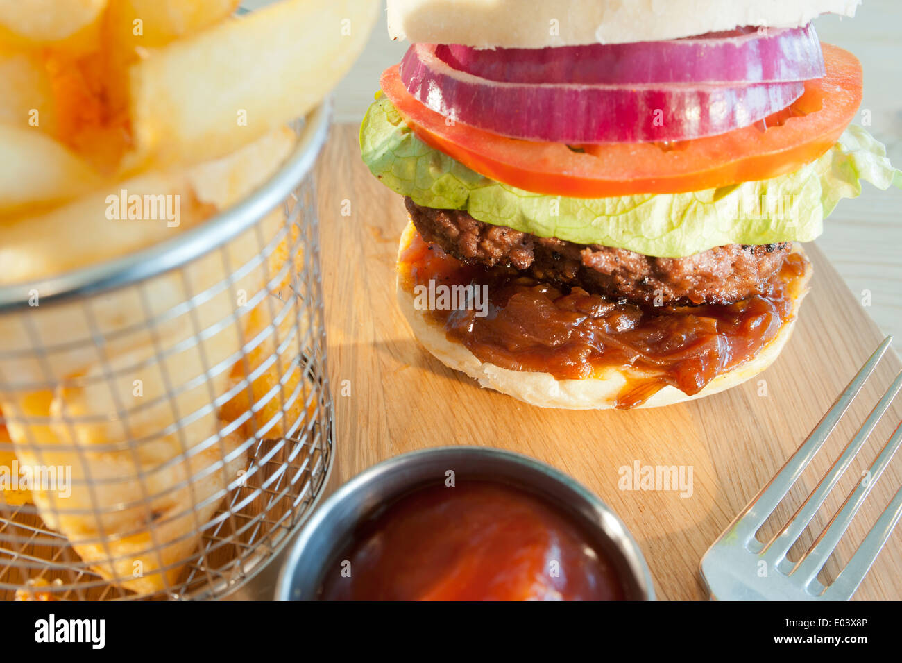 Classic burger and salad with side order of French fries or chips and tomato ketchup on a wooden plate - Stock Image