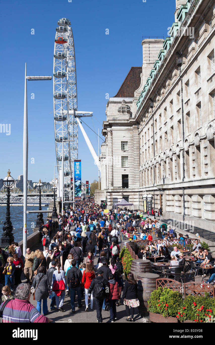 Crowds on the embankment outside County Hall, London. - Stock Image