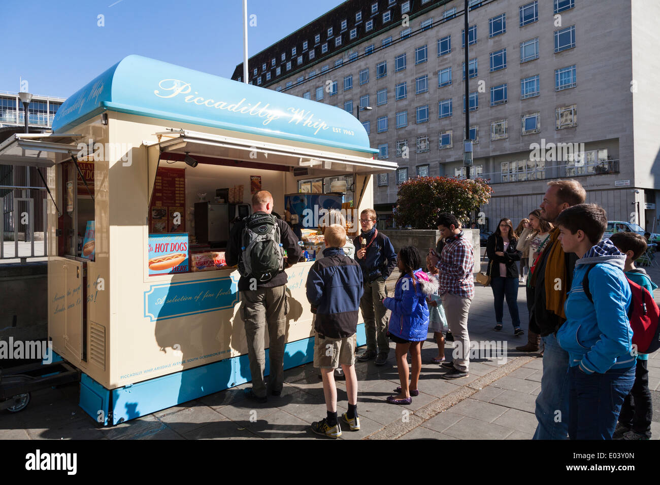 People buying fast food from hotdog and ice cream kiosk. - Stock Image