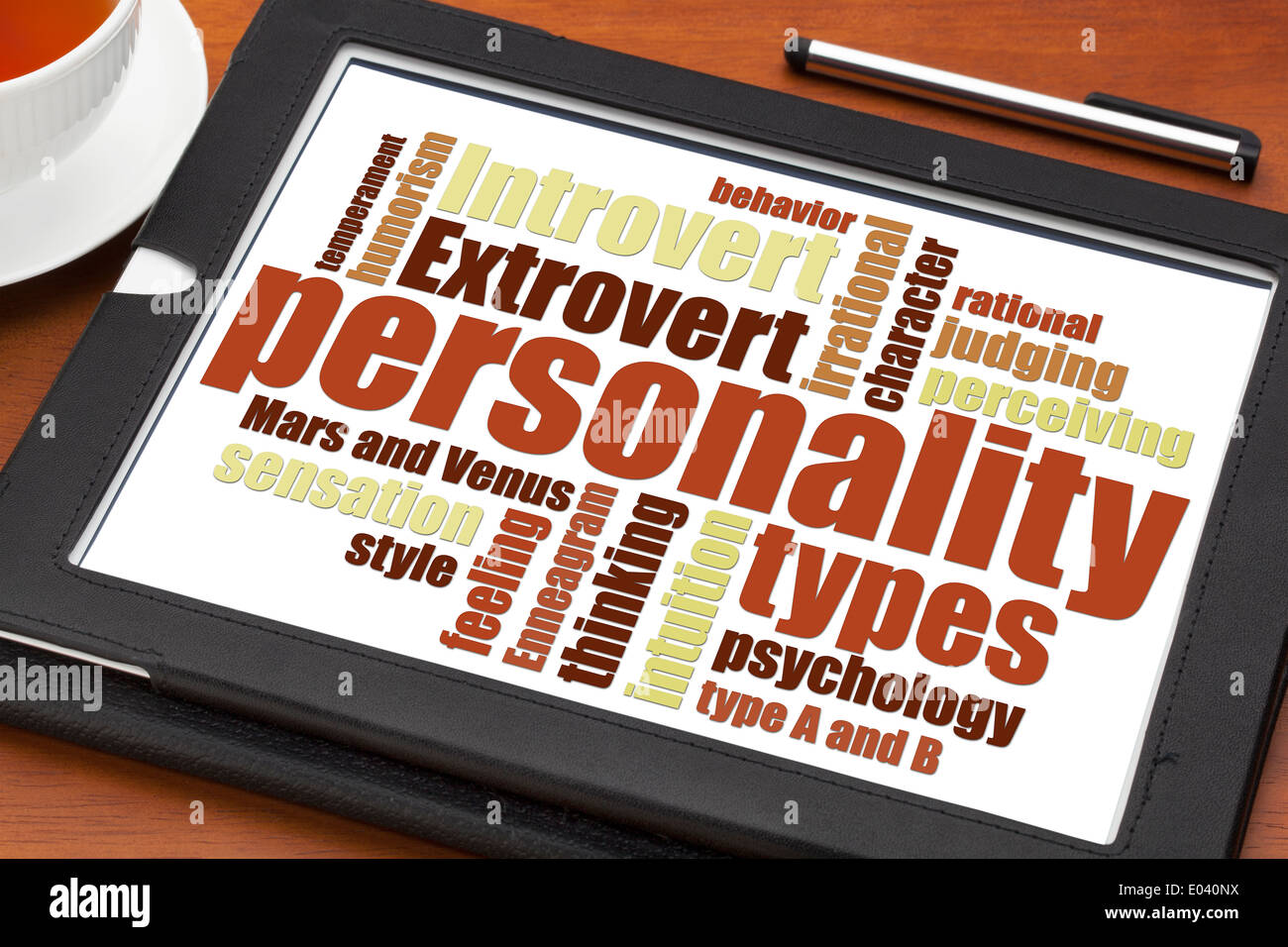personality types word cloud on a digital tablet with a cup of tea - Stock Image