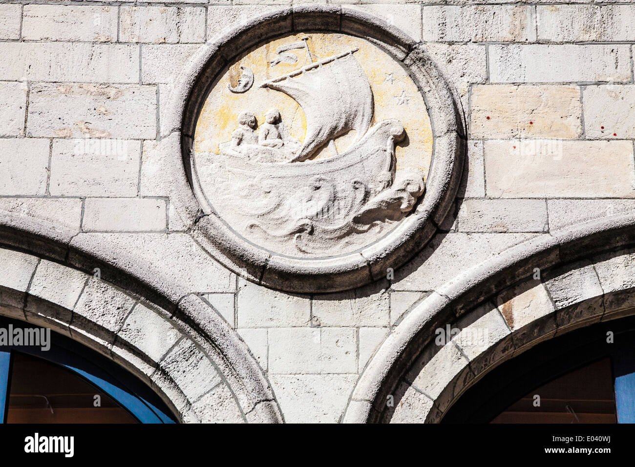 Stone carving of an old sailing boat on a wall in Antwerp, Belgium. - Stock Image