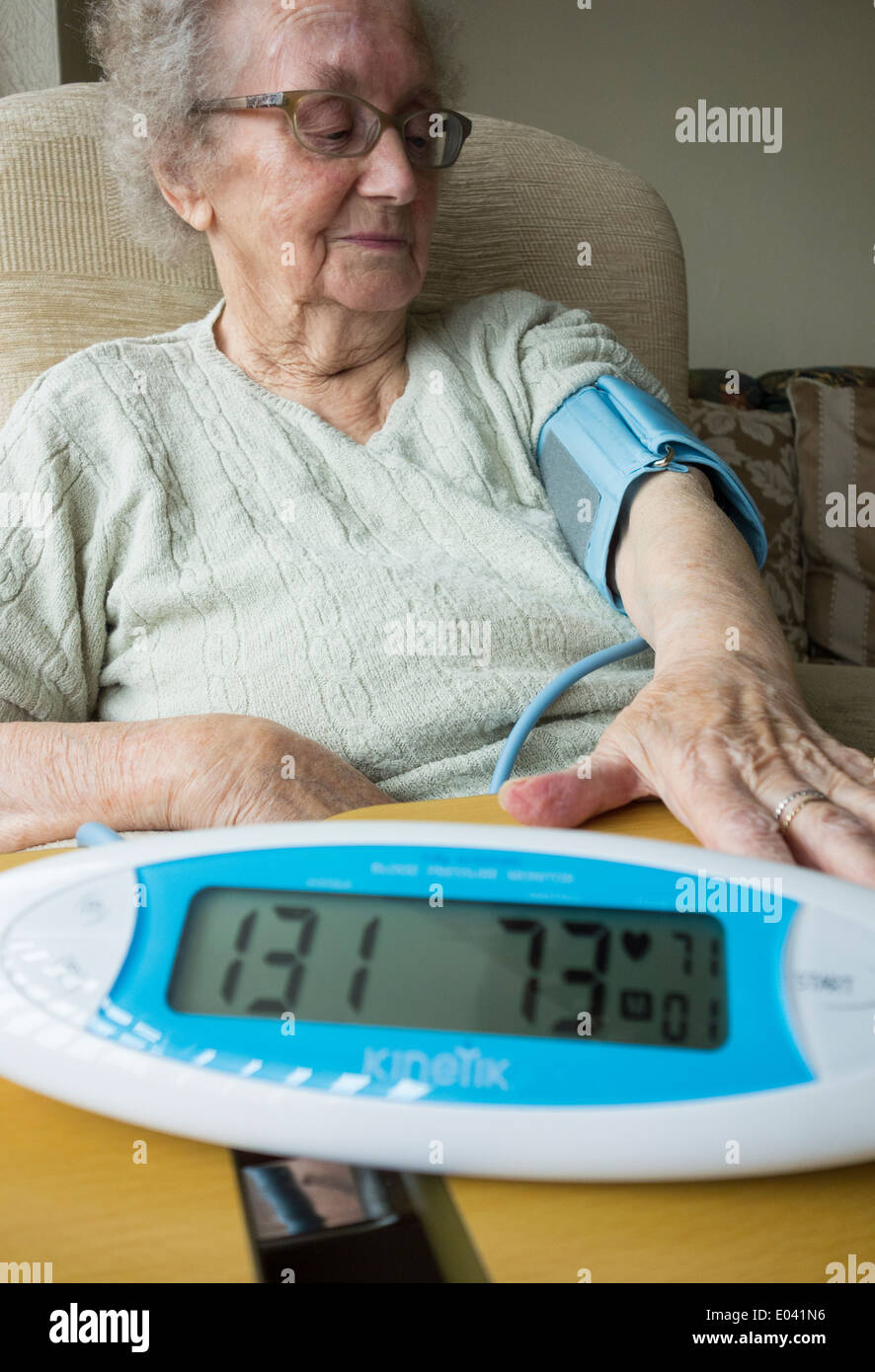 Elderly lady in her nineties having Blood Pressure ckecked at home - Stock Image
