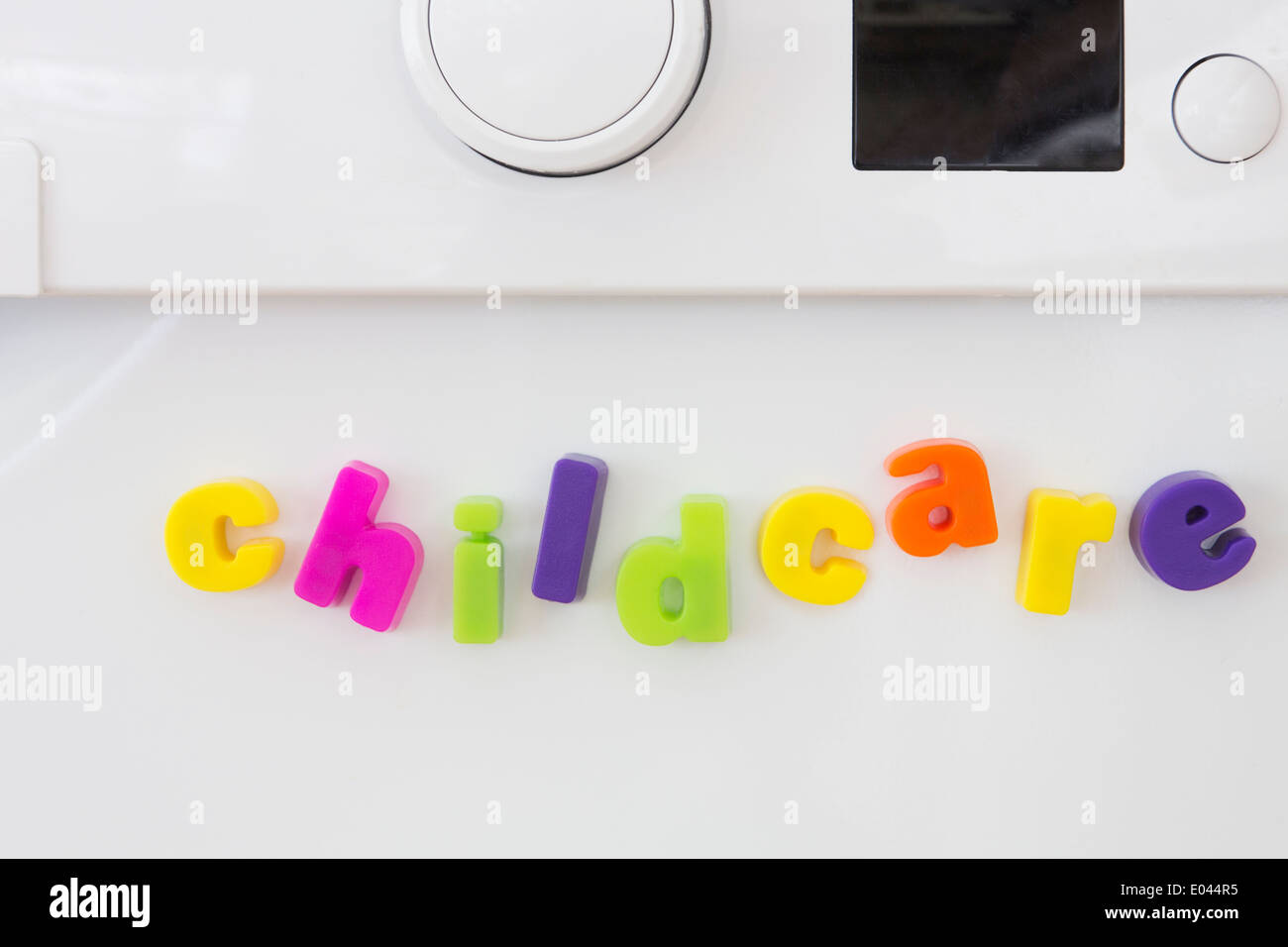 Toy Magnetic Letters Spelling Out Childcare On Washine Machine - Stock Image