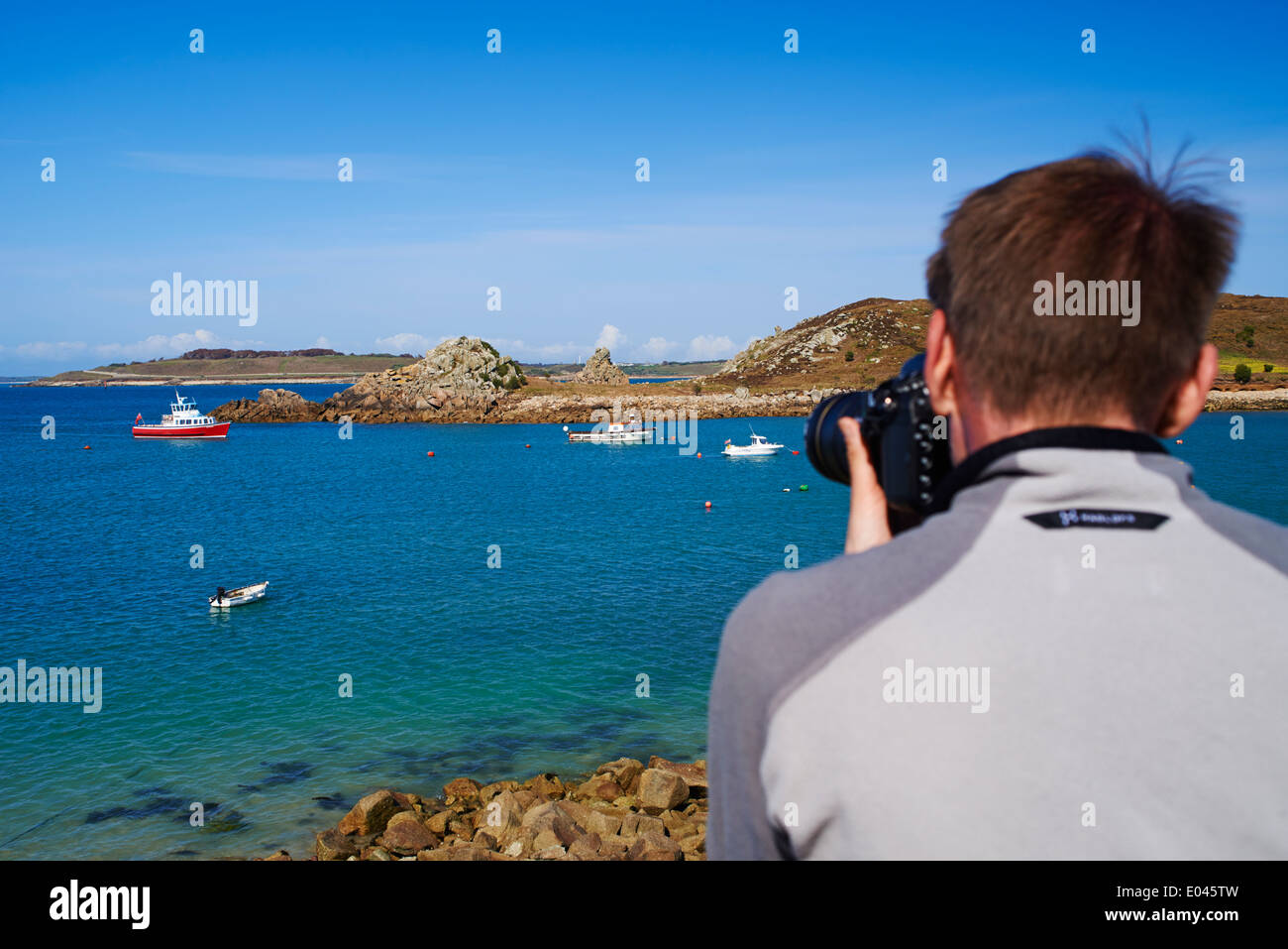 Man taking a photograph of the stunning views at St Agnes and Gugh, Isles of Scilly, Scillies, Cornwall in April Stock Photo
