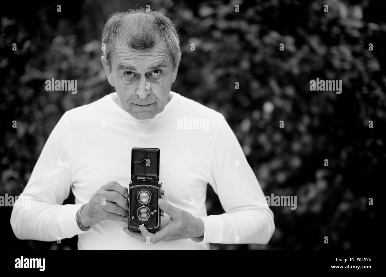 Senior man photographer with Rolleiflex twin lens reflex film camera - Stock Image