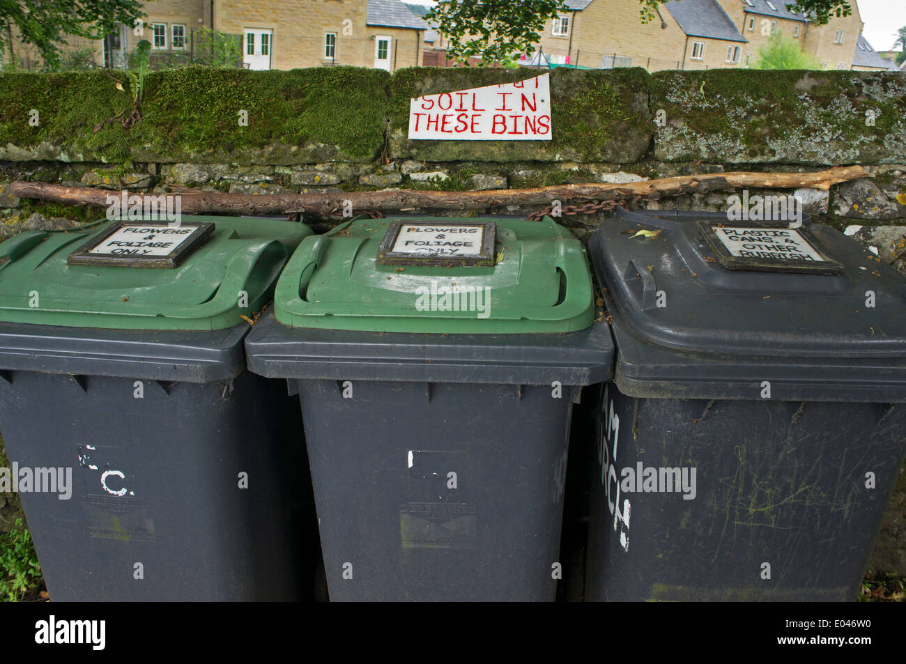 Close-up of grey & green environmentally-friendly recycling bins, labelled & lined-up in churchyard of Eyam Parish Stock Photo