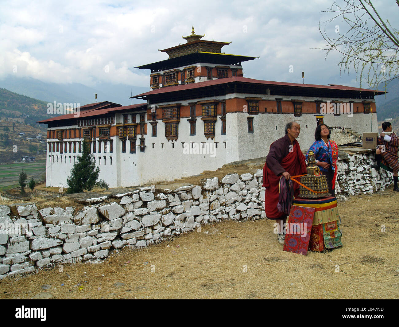 A vendor at the Tsechu Festival in Paro with the Paro Dzong in the background,Bhutan - Stock Image