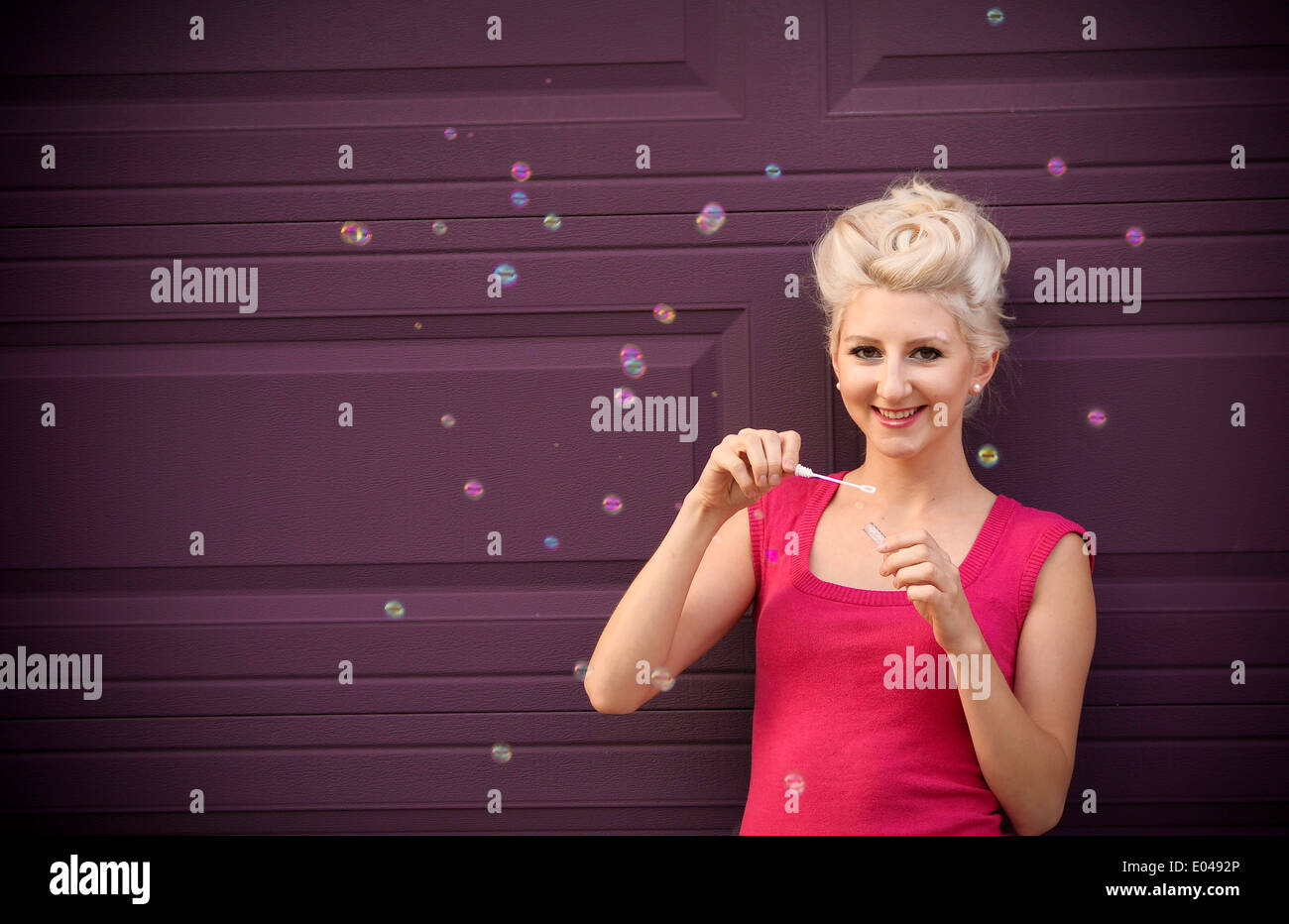 Blond girl blowing bubbles in a pink shirt in front of a purple wall - Stock Image