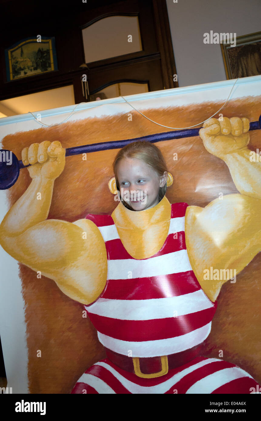 Polish girl age 10 with her face in hole posing as a muscular weight lifter. Zawady Central Poland - Stock Image