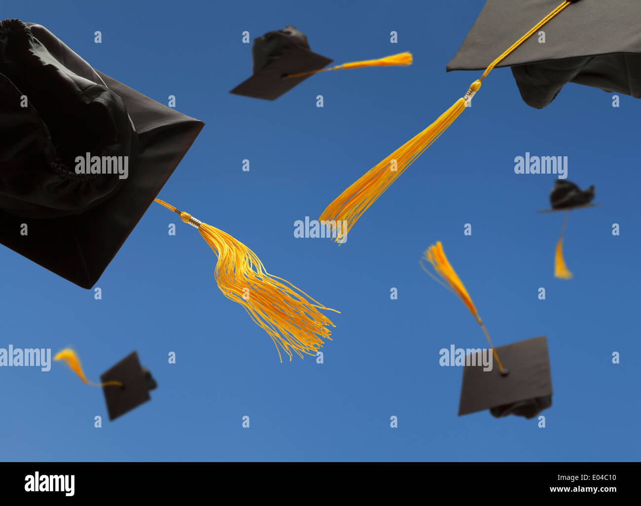 Black Graduation Hat Toss into the Air with Yellow Tassels - Stock Image