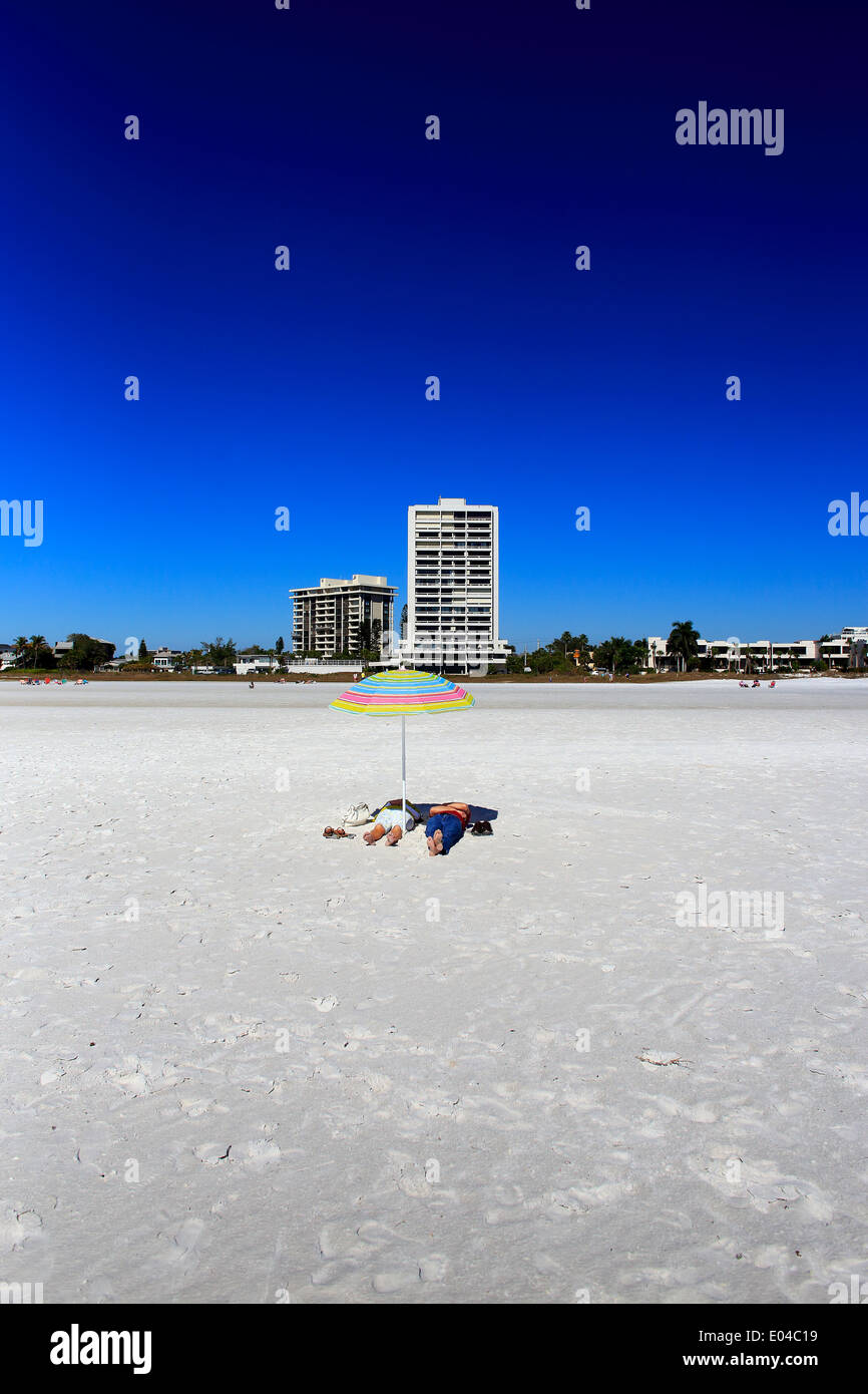 An unrecognizable couple under an umbrella laying on the sand on Siesta Key Beach in Sarasota, Florida, USA - Stock Image
