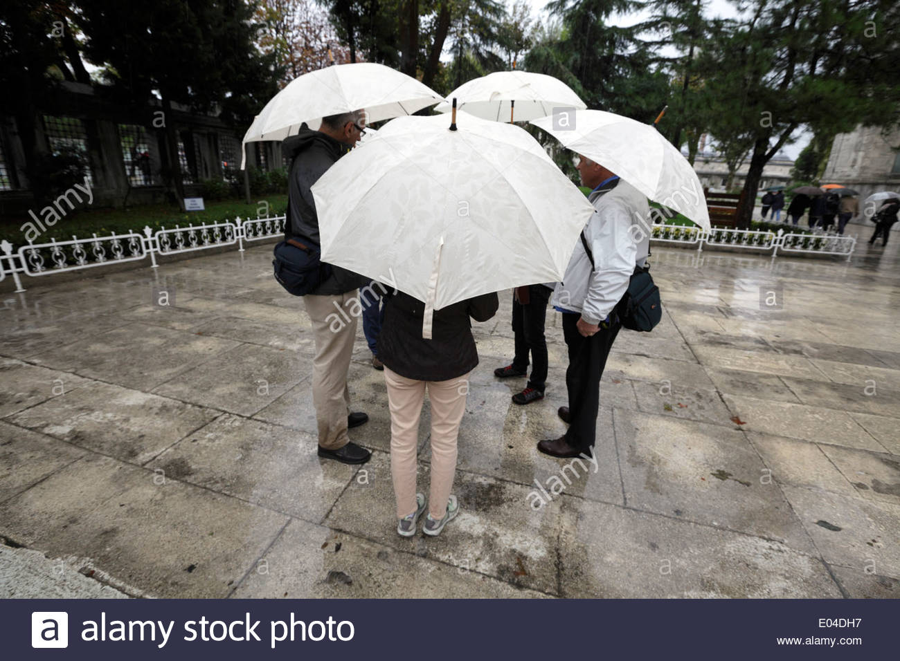 group of people together on a wet rainy day all with same umbrella - Stock Image