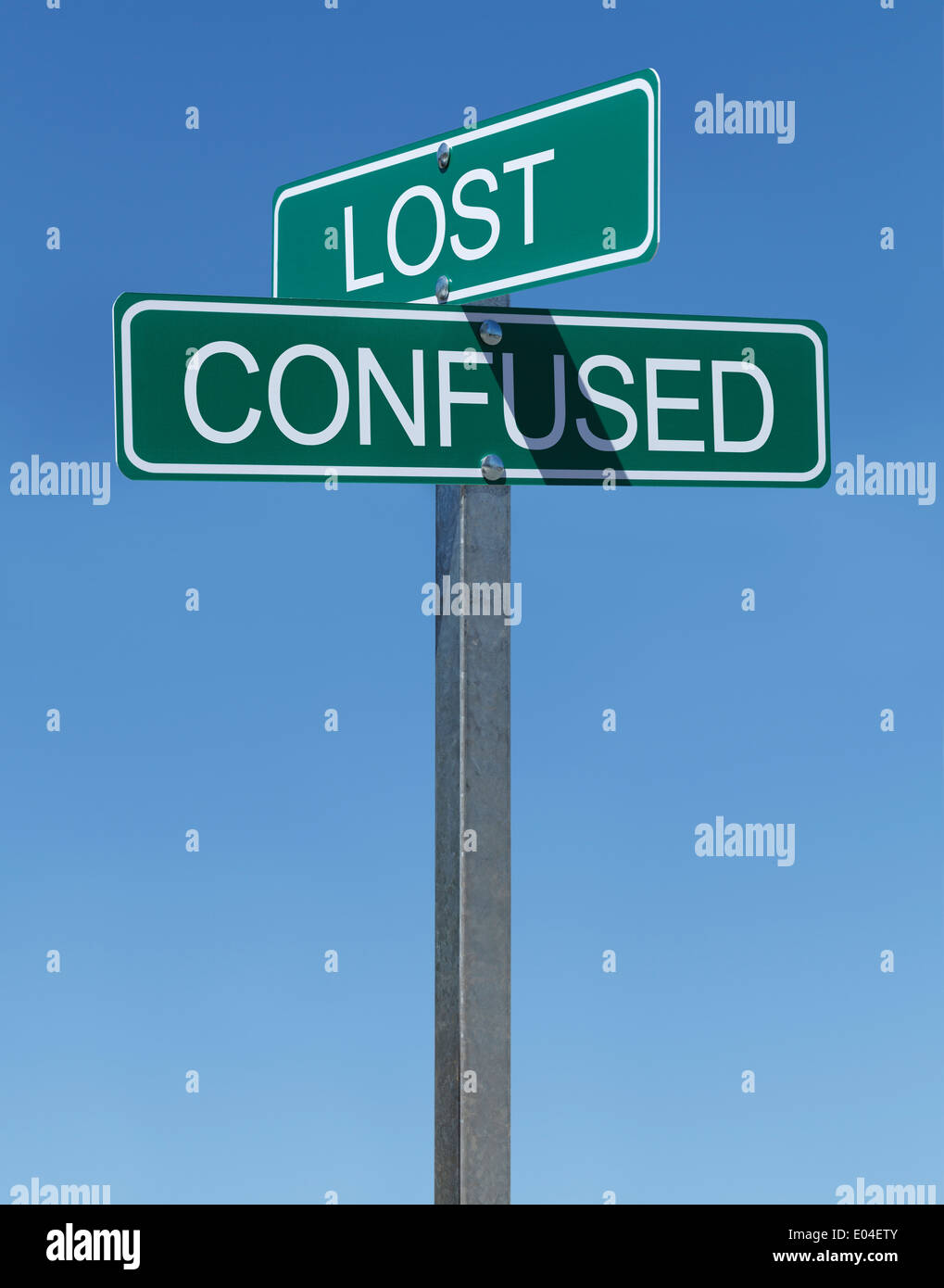 Two Green Street Signs Lost and Confused on Metal Pole with Blue Sky Background. - Stock Image