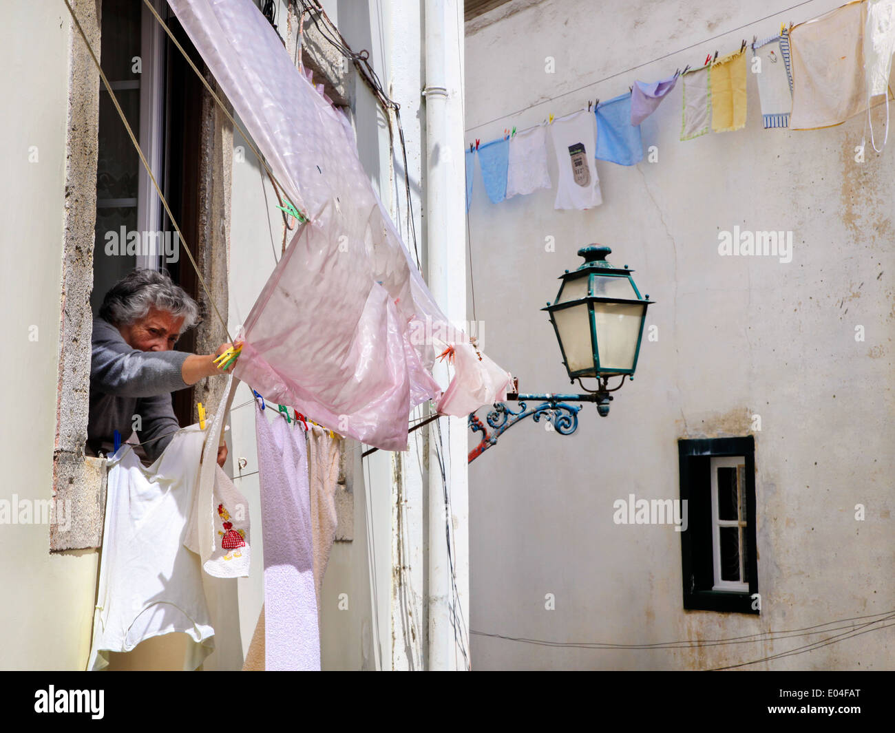 Woman in daily routine in Alfama, Lisbon - Stock Image