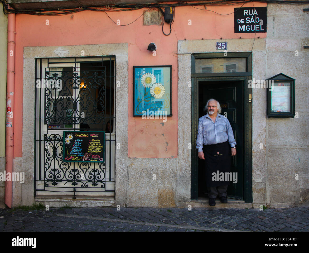 Man in front of a restaurant in Alfama, Lisbon - Stock Image