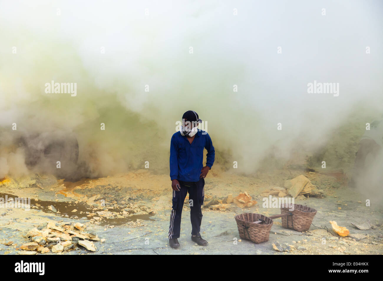 Sulfur miner wearing gas mask, Kawah Ijen, Banyuwangi Regency, East Java, Indonesia - Stock Image