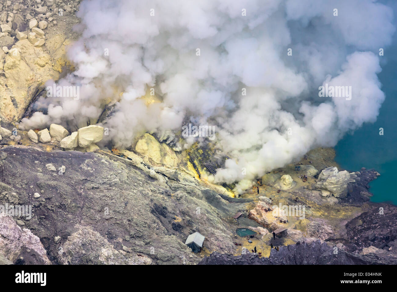 Sulfur mine near turquoise acid crater lake, Kawah Ijen, Banyuwangi Regency, East Java, Indonesia Stock Photo