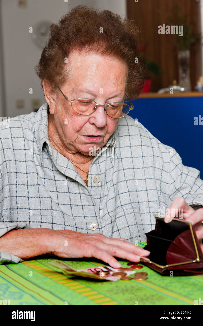 Old woman counts here money, Alte Frau zaehlt ihr Geld - Stock Image