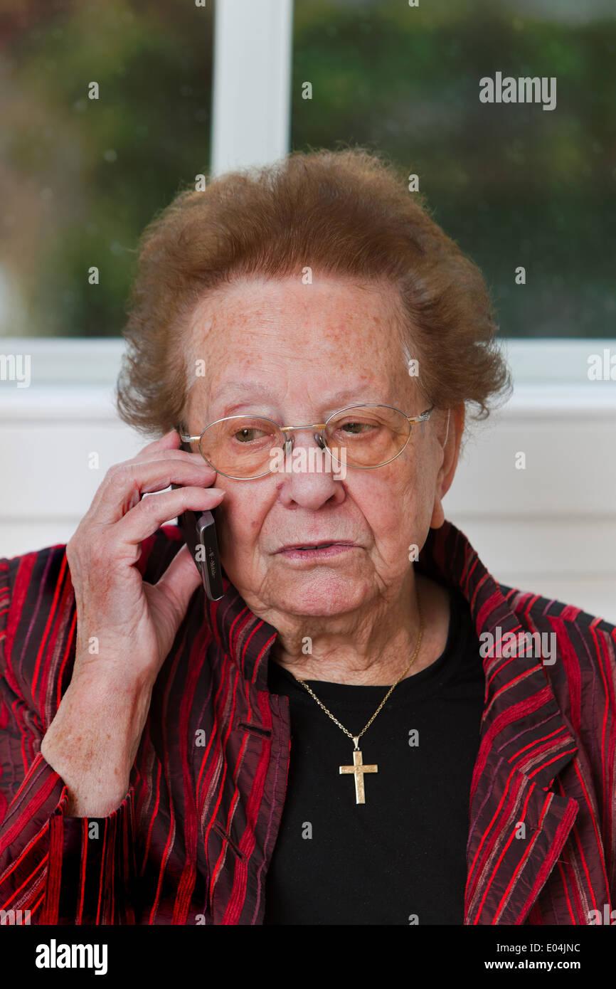Old woman makes a phone conversation with mobile phone, Alte Frau fuehrt ein Telefon Gespraech mit Mobiltelefon - Stock Image