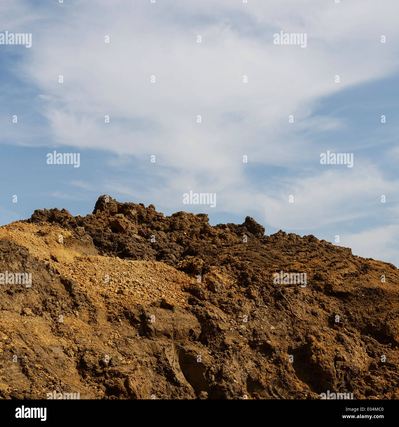 Pile of earth against a blue sky on a UK construction site - Stock Image