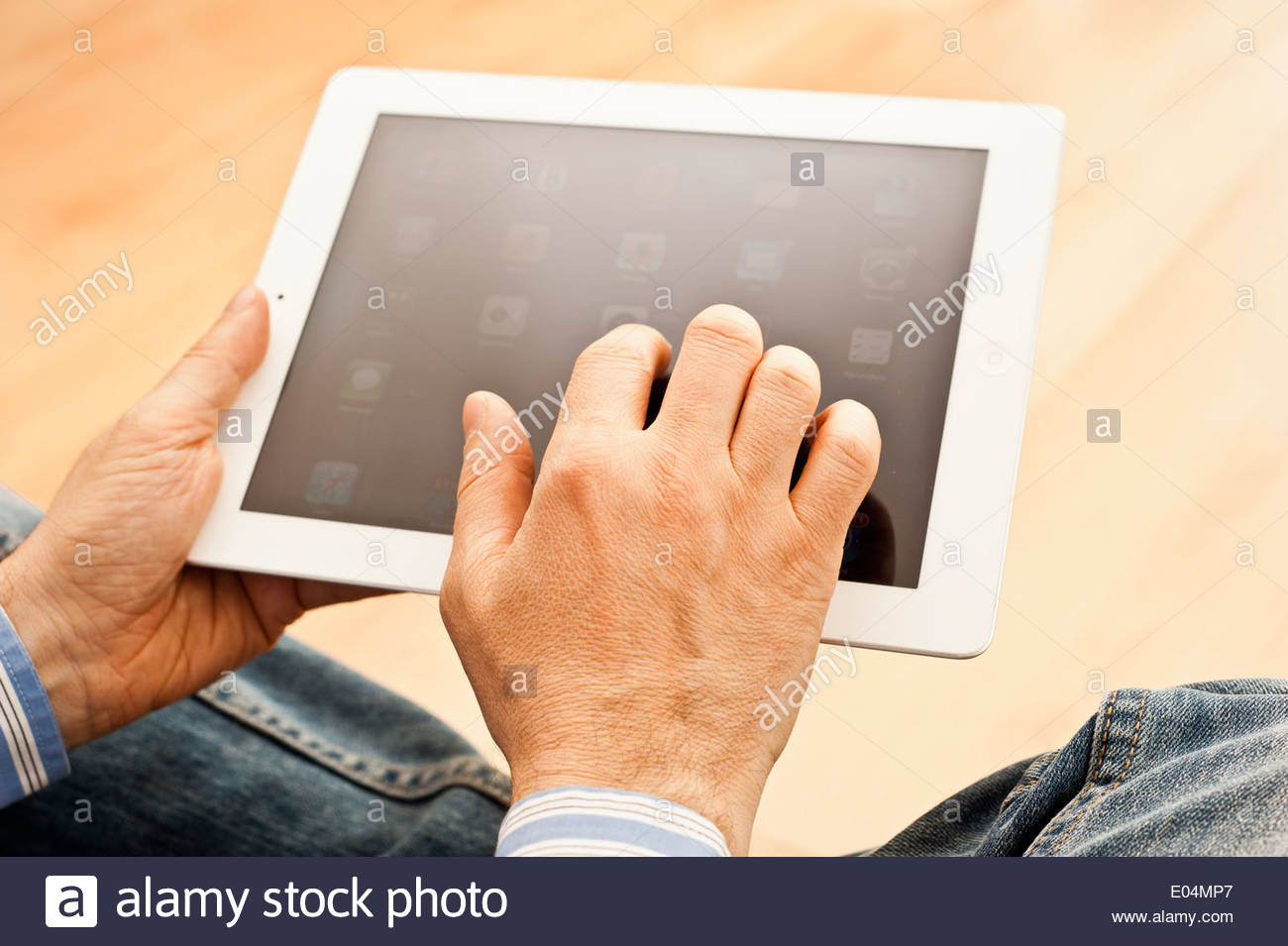 man hands holding and using a tablet computer - Stock Image