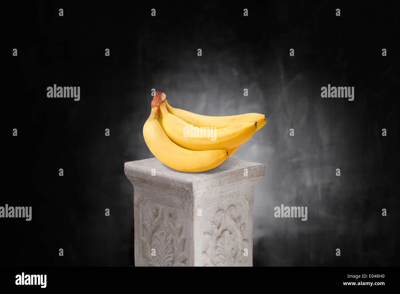 Bunch of yellow bananas on a pedestal. - Stock Image