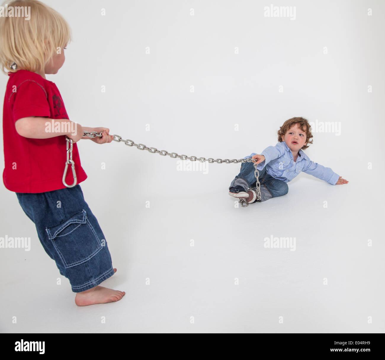 boys playing with chains, tug of war, studio shot - Stock Image