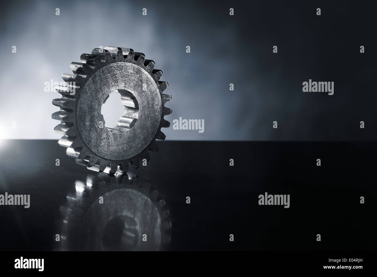 Old cog gear wheel on reflecting metal background. Short depth-of-field. - Stock Image