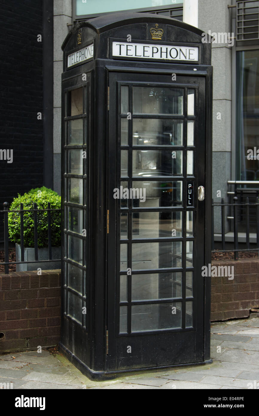 English Phone Box, painted black instead of the traditional red. - Stock Image